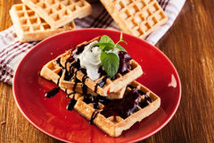 Waffles with chocolate sauce, whipped cream and confiture Royalty Free Stock Image