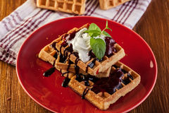 Waffles with chocolate sauce, whipped cream and confiture Royalty Free Stock Photography