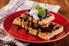 Waffles with chocolate sauce, whipped cream and confiture Stock Images