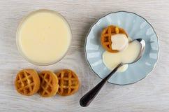 Waffles, colher de chá com leite condensado nos pires, bacia com leite condensado, waffles na tabela Vista superior imagem de stock