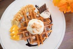 Waffles com banana, laranja e gelado na placa branca Foto de Stock Royalty Free