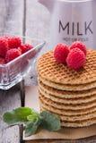Waffles com framboesas e chá do leite para o café da manhã em um de madeira Imagens de Stock