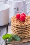 Waffles com framboesas e chá do leite para o café da manhã em um de madeira Fotos de Stock Royalty Free