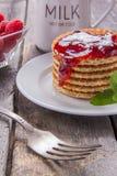 Waffles com framboesas e doce para o café da manhã em uma tabela de madeira Fotos de Stock