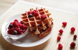 Waffles com mel, doce, e bagas em uma placa branca Fotografia de Stock Royalty Free