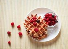 Waffles com mel, doce, e bagas em uma placa branca Fotos de Stock