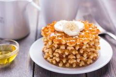 Waffles com mel e uma banana para o café da manhã Imagem de Stock