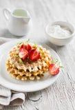 Waffles com morangos em uma placa branca Imagens de Stock