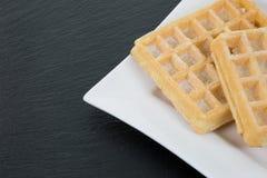 Waffles com pó em uma placa branca no lado direito com cópia Imagens de Stock