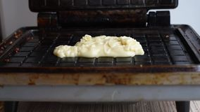 Preparation of wafers from fresh dough in a waffle maker in daylight. Waffles. Cooking fresh hot waffles in a waffle maker stock footage