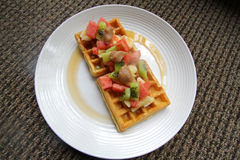 Waffles covered with  fruit and maple syrup Royalty Free Stock Photography