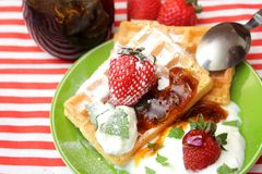 Waffles with cream and berries. A dessert of some waffles with cream and strawberries royalty free stock images