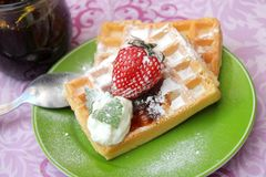 Waffles with cream and berries. A dessert of some waffles with cream and strawberries royalty free stock photos
