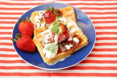 Waffles with cream and berries. A dessert of some waffles with cream and strawberries stock images