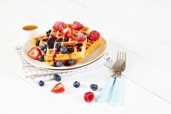 Waffles dourados com bagas e copo do mel Imagens de Stock