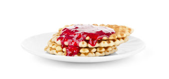 Waffles drenched raspberry jam on a white plate Stock Images