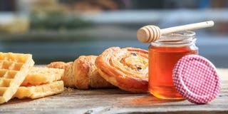 Waffles e mel em uma tabela de madeira imagens de stock