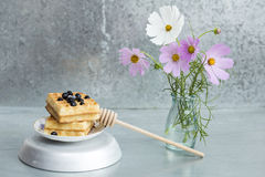 Waffles and flowers. On a metal background royalty free stock image