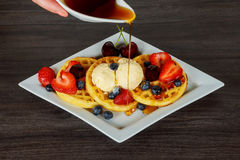 Waffles with fresh berries, whipped cream and ice cream. Wafers with blueberries of strawberries and ice cream Royalty Free Stock Images