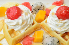 Waffles with fresh fruits and cream. On white plate Royalty Free Stock Image