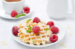 Waffles with fresh raspberries, almonds and tea for breakfast Stock Photo