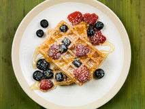 Waffles With Fresh Raspberries and Blueberries. Healthy Breakfast of Waffles With Fresh Raspberries and Blueberries and Honey or Syrup and Icing Sugar Royalty Free Stock Photo