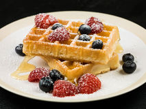 Waffles With Fresh Raspberries and Blueberries. Healthy Breakfast of Waffles With Fresh Raspberries and Blueberries and Honey or Syrup and Icing Sugar Stock Photos