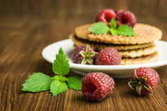 Waffles and fresh raspberries. On a wooden background Royalty Free Stock Photography
