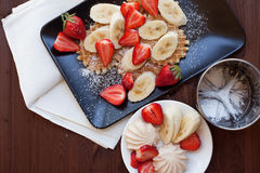 Waffles with fresh strawberries and bananas on rustic wooden background. Top view Royalty Free Stock Images