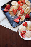 Waffles with fresh strawberries and bananas on rustic wooden background. Top view Stock Image
