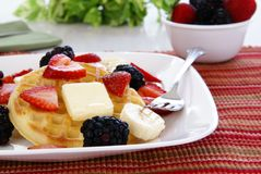 Waffles and Fruit. Waffles with strawberries, blackberries, bananas, butter, and light vanilla syrup Royalty Free Stock Images