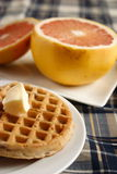 Waffles and fruit. A waffle on a plate topped with butter and a grapefruit in the background Stock Images