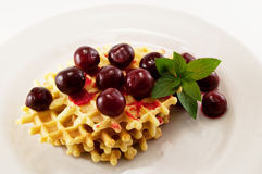 Waffles with fruit. Waffles with fresh cherries and mint on a white plate Royalty Free Stock Photos