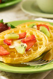 Waffles with fruits and syrup Stock Images