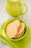 Waffles  in the green bowl with jug of milk. Waffles in the green ceramic bowl with jug of milk on the old retro kitchen table Royalty Free Stock Image