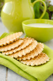 Waffles on a green table napkin. Waffle dessert on a green table napkin. Green ceramic bowl with milk and jug on background Royalty Free Stock Photo