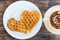 Waffles heart shaped on white plate and coffee cup. Stock Image