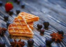 Waffles hearts with blueberry and strawberry tied with a string on the dark wooden background royalty free stock photo