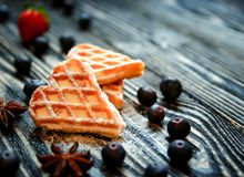 Waffles hearts with blueberry and strawberry on the dark wooden background. royalty free stock photos