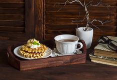 Waffles with honey and cream, a cup of tea in a vintage tray, a stack of old books on brown wooden table. Royalty Free Stock Images