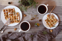 Waffles with honey, nuts, coffee and herbs, sweet dessert breakfast. Stock Photography