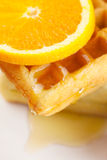 Waffles,honey and orange on a plate isolated on white Royalty Free Stock Photo
