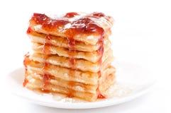 Waffles with honey, strawberry jam and sugar. Pile of waffles with honey, strawberry jam and powdered sugar on white background Stock Photo