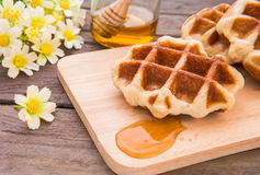 Waffles with honey on wooden plate Stock Photography