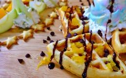 Waffles, ice cream, fresh fruit. Traditional Belgian waffles with ice cream and fruit Stock Photos