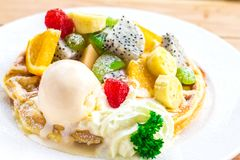 The Waffles, ice cream and fruit in dish on table. Stock Photo