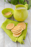 Waffles with jug of milk. Waffles on a green napkin and in ceramic bowl with jug of milk on the old retro kitchen table Royalty Free Stock Images