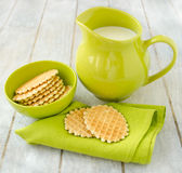 Waffles with jug of milk. Waffles on a green napkin and in ceramic bowl with jug of milk on the old retro kitchen table Stock Images