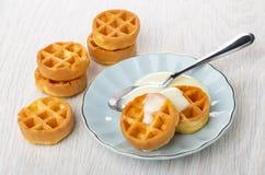 Waffles macios, colher com leite condensado em uns pires, poucos waffles redondos na tabela fotos de stock royalty free