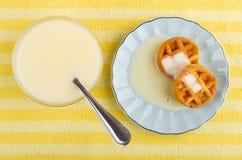 Waffles macios com leite condensado nos pires, bacia com leite condensado, colher no guardanapo amarelo Vista superior foto de stock royalty free